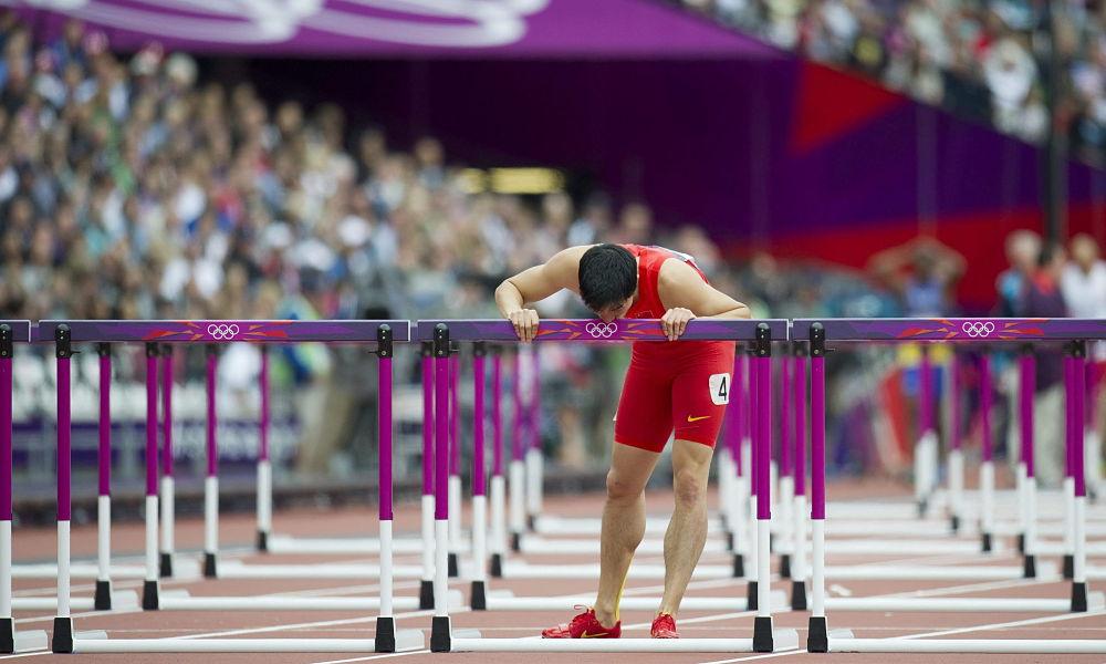 LOND02 LONDRES (REINO UNIDO) 07/08/2012.- El atleta chino Xiang Liu muestra su frustración al perder una de las mangas de clasificación de los 110m valla masculino de la competición de Atletismo al chocar con una valla en los Juegos Olímpicos de Londres (Reino Unido) hoy, martes 7 de agosto de 2012. EFE/ JEAN-CHRISTOPHE BOTT